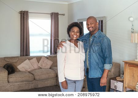Portrait of a smiling African couple affectionately standing together in their living room at home