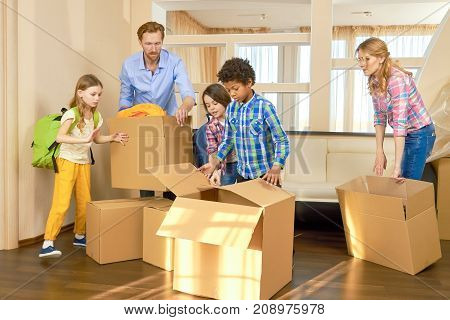 Parents and children relocation. Family moving out boxes.