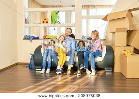 Family relaxing after relocation. Parents and children, cardboard boxes.