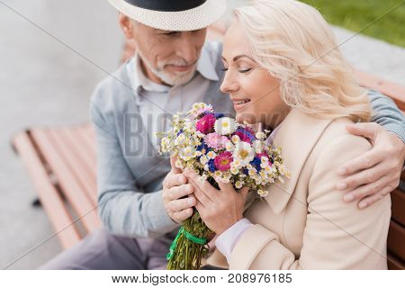 Two pensioners are sitting on a bench in the alley. The aged man gave the woman flowers. She is delighted with the gift. He gently embraces her