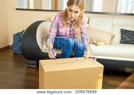 Girl writing on cardboard box. Young woman indoors, relocation.