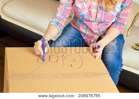 Hands writing on cardboard box. Woman getting ready for relocation.
