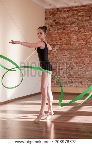 Young ballerina repetition. Rhythmic gymnastics. Teenage sport, healthy teen lifestyle. Confident girl with green ribbon, dance class background, exercise concept