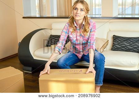 Thoughtful woman and cardboard box. Young person, relocation. How to plan a move.
