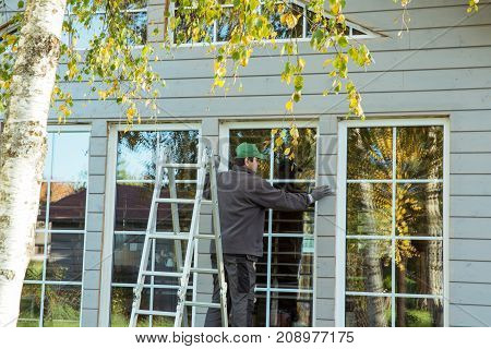 The worker makes painting of the facade of the wooden frame house after installation of windows. Construction worker thermally insulating eco wooden frame house with wood fiber plates