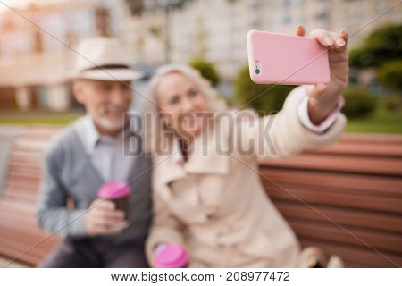 Two pensioners are sitting on a bench with a glass of coffee in their hands. They smile and do selfie on a woman's smartphone, sitting together