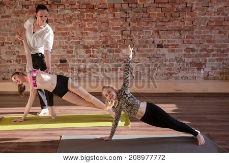 Gymnastics exercises. Healthy children lifestyle. Teenage sport with female instructor, yoga for kids. Happy stretching girls in studio. Gym wall background with free space, health concept