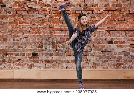 Dance is life. Happiness in moving. Sporty teenage girl, brick wall background with free space. Hip hop lifestyle, flexible dancing young female, breakdance concept