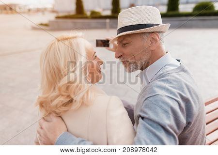 Two pensioners sit on a bench and look at each other with tenderness. Before them a beautiful square
