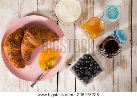 Breakfast with croissant blueberries yogurt orange and blueberry jam over a wooden table seen from above