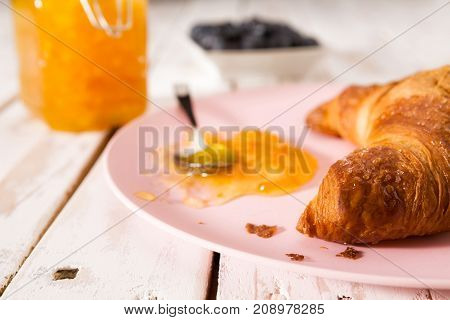 Closeup of croissant and orange jam on a pink plate over a wooden table