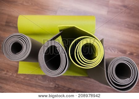 Life with yoga. Modern exercise interior. Gym wooden background, bright place for gymnastics with mats top view. European style in focus on foreground, fitness concept