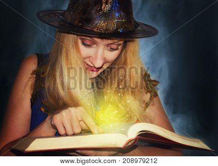 Good witch in the hat reads magic spells in the book on the fog background.
