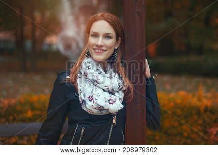 Young redhead woman smile posing in park at autumn