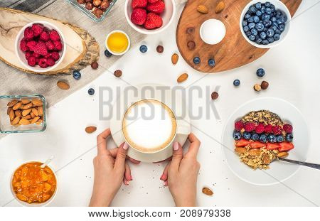 Good morning - healthy breakfast background with oatmeal coffee, berries, egg, nuts. Coffee, hands, hold, cup. White wooden food background