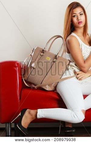 Fashion clothes clothing accessories trendy outfits concept. Woman wearing light outfit and black high heels sitting on red sofa presenting leather bag