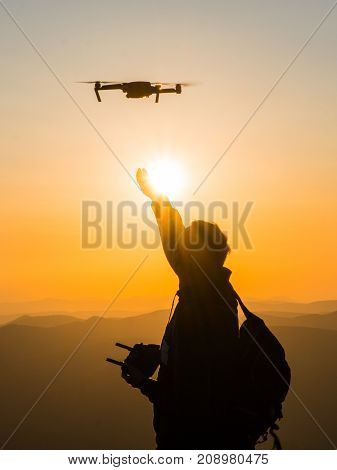 Silhouette of young man using drone at sunset for photos and video making - Happy man having fun with new technology trends in mountains - Youth and digital concept.
