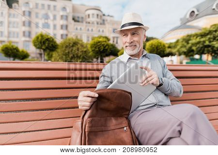 A pensioner sits on a bench in a beautiful square. He takes out a gray tablet from his brown briefcase