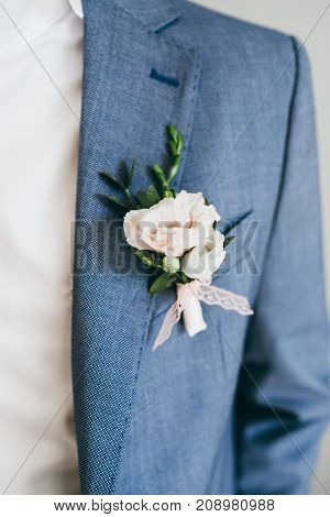 Wedding. Close up image of beautiful boutonniere on the groom's jacket. Soft focus on boutonniere. Artwork.