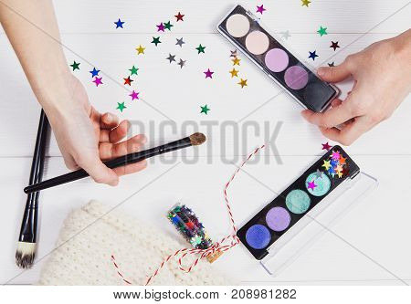 Flat lay with hands holding visage brush and eye shadows. Accessories and decorations on the white wooden background. Concept Christmas make-up