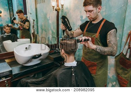 Man Getting Trendy Haircut At Barber Shop. Male Hairstylist In Tattoos Serving Client, Drying Hair W