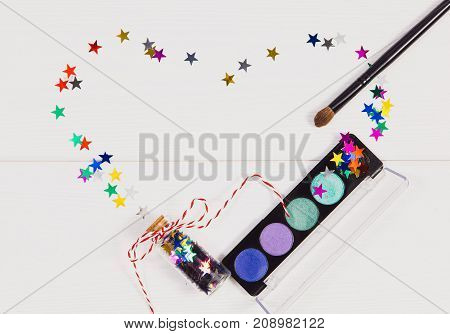 Decorative flat lay composition with makeup products, cosmetics and glass jars with decorative colored stars. top view on white wooden background. Concept Chrismas, New years evening make-up .
