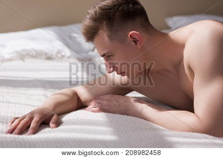 Frustrated man lying on bed after painfull love fight with girlfriend. Relationship love problems at home.