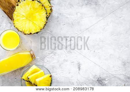 Non-alcoholic beverages. Bottle with fruit juice near pineapples slices on grey background top view.
