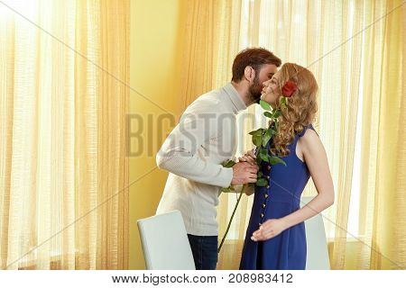 Young couple and rose. Man kissing woman on cheek. Let love bloom.