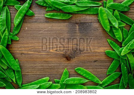 Fresh pea pods on dark wooden background top view.