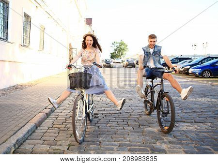 Couple in love. Happy young couple going for a bike ride on a summer day in the city.They are having fun together.