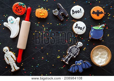 Cook halloween gingerbread cookies bat, skeleton, ghost. Sweets near rolling pin on black background top view.