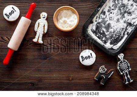 Cook halloween gingerbread cookies in shape of skeleton, mummy. Sweets near desk and rolling pin. wooden background top view.