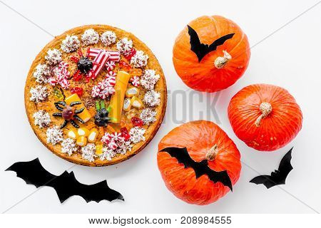 Pie for halloween with gummy spiders on white background top view.