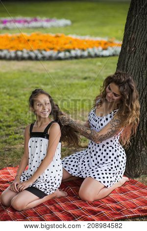Beautiful hairstyle. Creative friends picnic. Modern youth life, happy stylish sisters, active beauty with nature background. Leisure activity outdoors, happiness, mother care concept