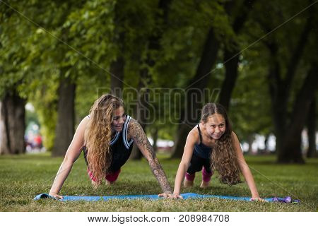 Family teamwork gymnastics. Active stretching outdoors. Yoga training exercise, healthy beauty, teenage sport with coach. Nature background, fun entertainment outside