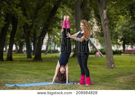 Active teenage sport. Strong family beauty. Stretching exercise, teamwork gymnastics with coach, healthy beautiful lifestyle. Nature background, creative entertainment outdoors