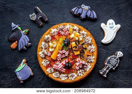 Halloween bakery and sweets. Pumpkin pie, gummy spiders, gingerbread cookies on black background top view.