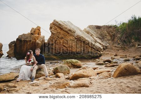 Outdoor beach wedding ceremony near the ocean, romantic happy couple sitting on stones at the beach.