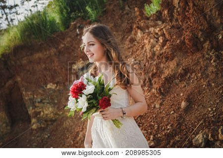 Outdoor beach wedding ceremony, stylish happy smiling bride with bouquet of flowers.