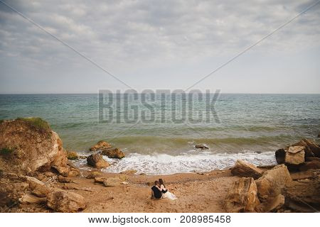 Outdoor beach wedding ceremony, stylish wedding loving couple is sitting near the sea.