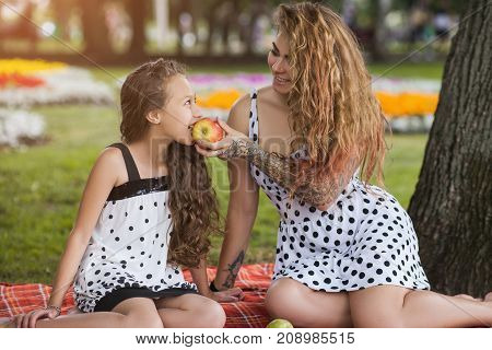 Family picnic. Healthy summer style. Mother care for teenager, fruit diet, nature background. Happy leisure time outdoors, stylish and pretty females together