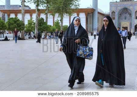 Fars Province Shiraz Iran - 19 april 2017: The inner courtyard of the Shah Cheragh Shrine two Muslim women dressed in a chador stroll after a prayer.