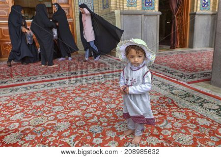 Shiraz Iran - 19 april 2017: Shah Cheragh Shrine Portrait of a unknown little girl about 4 years old standing in courtyard of the mosque on the background of women wearing muslim black chador.