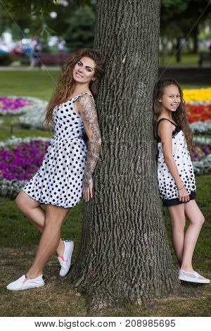 Beautiful summer style. Active family. Pretty young girls entertainment, park background. Stylish and happy female models