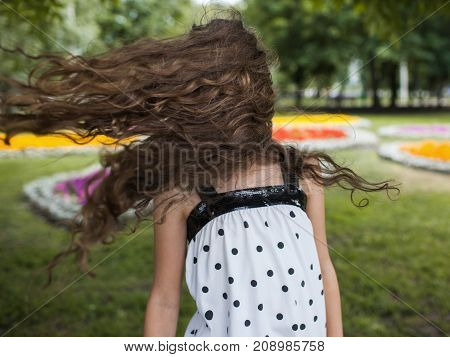 Summer happiness in motion. Strong wind. Unrecognizable teenage girl portrait, park background.