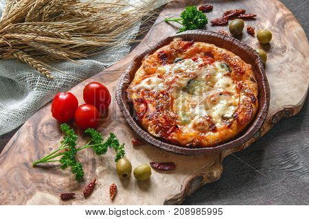 Round sausage pizza Margherita on a beautiful natural blackboard of olive . Selective focus. The horizontal frame.