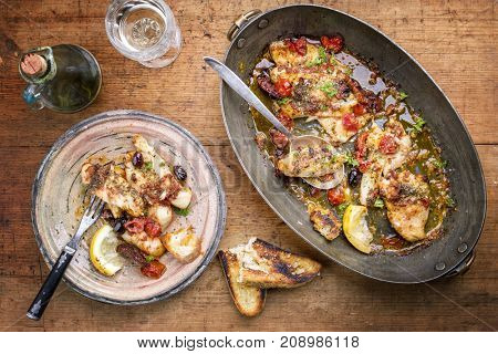 Fried John Dory fish fillet with vegetable and baguette as top-view in a casserole