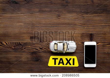 online order a taxi with mobile app and car model on wooden table background top view mockup