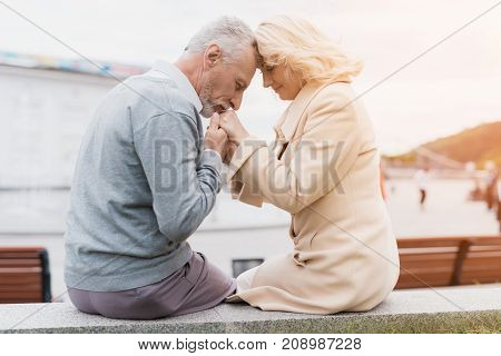 An elderly couple is sitting on the edge of a flower bed. They hold hands. The man gently kisses the woman's hands